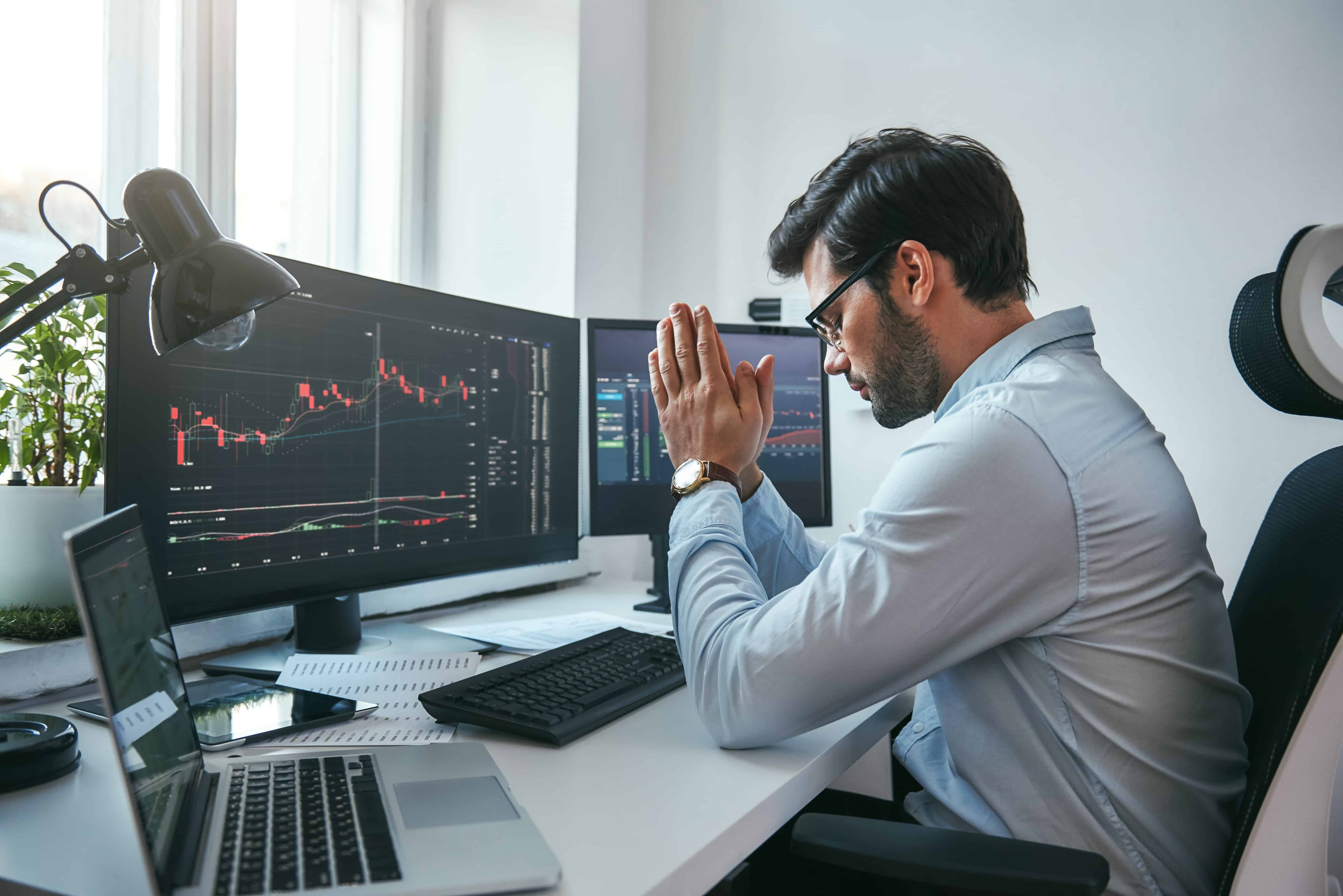 Young trader praying at his computer